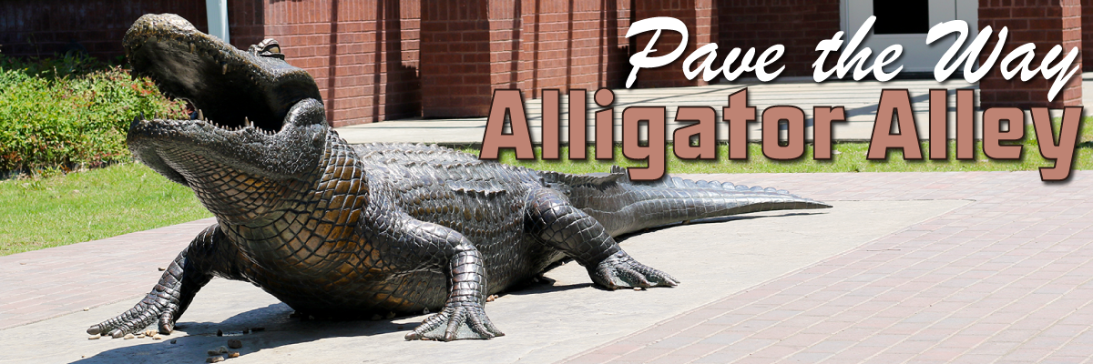 "A bronze statue of an alligator and text reading ""Pave the Way/Alligator Alley"""